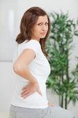 Donna dai capelli castani, toccando la schiena dolorosa — Foto Stock