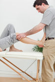 Brunette physiotherapist stretching a foot — Stock Photo