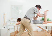 Brunette woman being stretched by a physiotherapist — Stock Photo