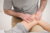 Physiotherapist massaging the knee of a woman — Stock Photo