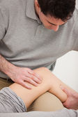 Physiotherapist looking at the knee of his patient — Stock Photo