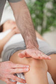 Physiotherapist using his hand palm to massage a knee — Stock Photo