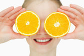 Close up of a cheerful woman placing oranges on her eyes — Stock Photo