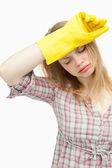 Tired woman wearing cleaning cloves — Stock Photo