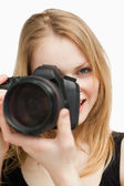 Blonde woman aiming with a camera — Stock Photo