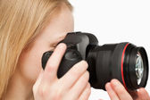 Close up of a young woman holding a camera — Stock Photo