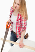 Woman using a wood saw — Stock Photo