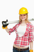 Cheerful woman holding a spirit level — Stock Photo