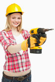 Woman using an electric screwdriver while smiling — Stock Photo