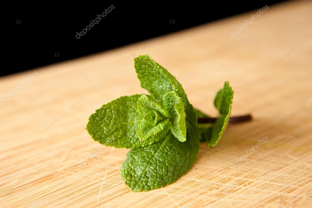 Mint on a chopping board against a black background — Stock Photo #13990987