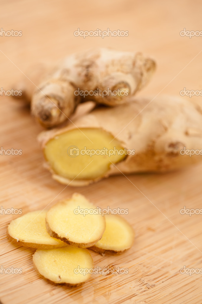 Slice of ginger and blurred piece of ginger on a worktop — Stock Photo #13991260