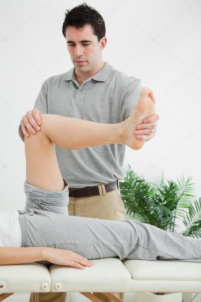 Brunette physiotherapist manipulating a leg in a room — Stock Photo #13992923