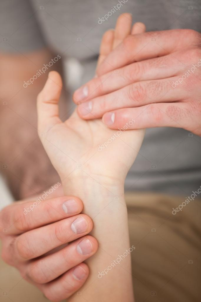 Doctor looking at the wrist of a patient in a room — Stock Photo #13993243