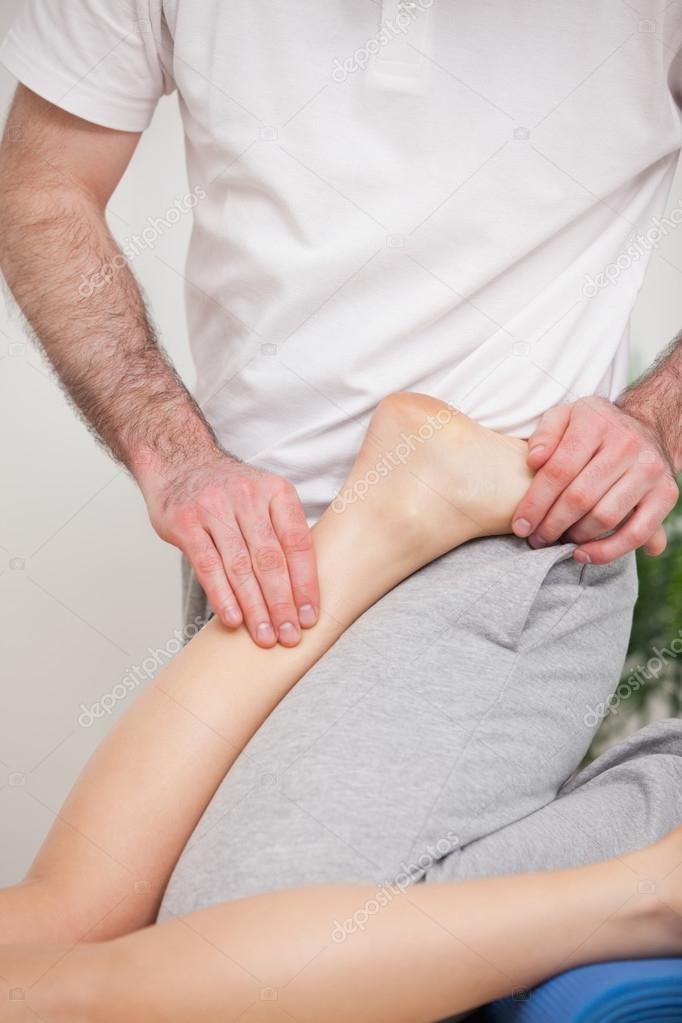 Podiatrist manipulating the ankle of his patient while putting his foot on him indoors — Stock Photo #13995115