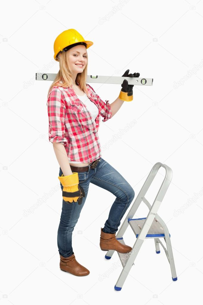 Woman holding a spirit level next to a step ladder against white background — Stock Photo #13996539
