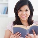 bir kitap okuyor iken bir kanepede oturan kadın — Stok fotoğraf
