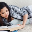 Stockfoto: Womreading book as she lays on floor