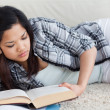 Stock Photo: Womreading book as she lays on floor