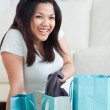 Smiling woman taking clothes off from a shopping bag — Stock Photo #14069798