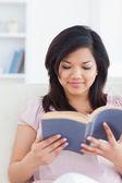 Kobieta siedzi na kanapie czytając książkę — Zdjęcie stockowe