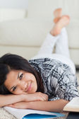 Woman crossing her legs and her arms as she lays on the floor — Stock Photo