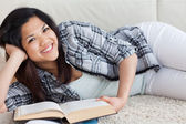Woman smiling and holding a book as she lies on the floor — Stock Photo