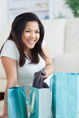 Smiling woman taking clothes off from a shopping bag — Stock Photo