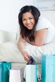 Frau auf der couch halten kleidung aus einer einkaufstasche — Stockfoto