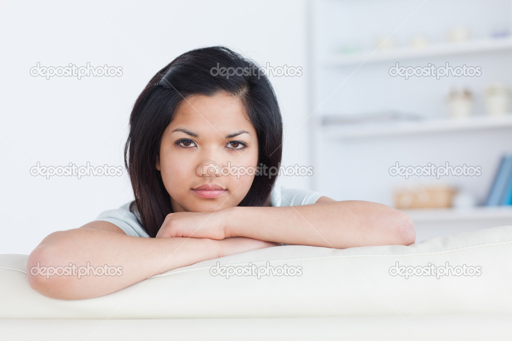 Woman crossing her arms on a white couch in a living room  Stock Photo #14069946