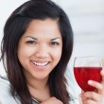 close-up de uma mulher sorridente segurando um copo de vinho tinto — Foto Stock