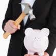 Businesswoman holding a piggy-bank and a hammer — Stok fotoğraf