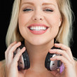 Photo: Happy blonde woman proudly holding her headphones