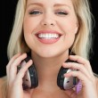 Foto de Stock  : Happy blonde woman proudly holding her headphones