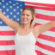Stock Photo: Joyful blonde woman holding the Stars and Stripes flag