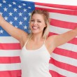 Joyful blonde woman holding the Stars and Stripes flag — Stock Photo