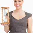 Woman smiling while holding a hourglass — Stock Photo