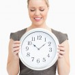 Woman looking at a clock in her hands — Stock Photo