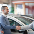 Smiling salesman shaking a customer hand — Stock Photo