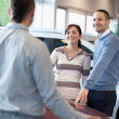Couple smiling and chatting with a salesman - Stock Photo
