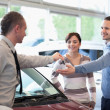Smiling couple receiving keys from a car dealer — Stock Photo