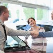 Car dealer shaking hand with smiling man — Stockfoto #14077291