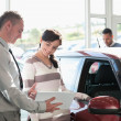 Smiling womchatting with car dealer — Stockfoto #14077293