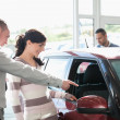 Car dealer pointing the interior of a car with a woman — Stockfoto