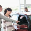 Car dealer pointing the interior of a car with a woman - Stock Photo