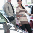 Salesman and a woman standing next to a car — Stock Photo