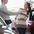 Smiling woman receiving keys from a salesman - Stock Photo