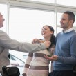 Laughing couple receiving keys from a salesman — Stock Photo #14077312