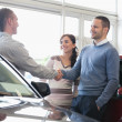 Man shaking a car dealer hand - Stock Photo