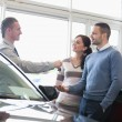 Smiling salesman handing keys to a couple — Stock Photo