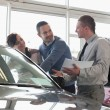 Salesman and a couple looking at a car — Foto de Stock